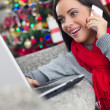 Smiling happy woman using using laptop and cell phone on Christm — Stock Photo