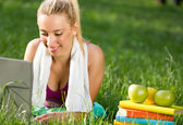 Frau nach ausübung in den park ausruhen und mit laptop — Stockfoto