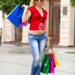 A shot of a woman with bags shopping outdoor — Stock Photo