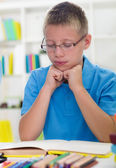 Young boy with glasses learns from books — Stock Photo