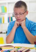 Ung pojke med glasögon lär sig från böcker — Stockfoto
