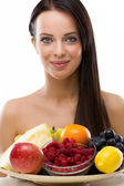 Beautiful young woman holding a plate with fresh fruit — Stock Photo