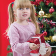 Pretty little girl smiling with present near the Christmas tree — Stock Photo