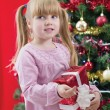 Pretty little girl smiling with present near the Christmas tree — Stock Photo #33967201