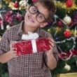 Pretty little boy smiling with present near the Christmas tree  — Stockfoto