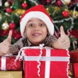 Little boy smiling with gift box near the Christmas tree — Stock Photo #33968715