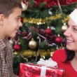 Mother gives boy a gift on Christmas night — Stock Photo