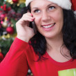 Happy young woman near Christmas tree making phone call — Stock Photo