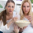Two Beautiful young woman watching TV and eating popcorn — Stock Photo
