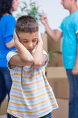 Sad boy in new home while parents quarreling — Stock Photo