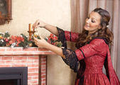Young woman decorates fireplace for Christmas Eve,retro style — Stock Photo