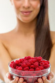 Beautiful woman holding a pot of raspberries — Stock Photo