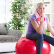 Stock Photo: Happy senior woman sitting on gym ball, and exercise