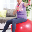 Senior woman sitting on gym ball, and exercise with weights at h — Stock Photo #35333395