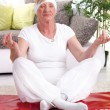 Smiling senior woman exercise yoga at home — Stock Photo