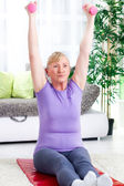 Senior woman exercise with weights at home — Stock Photo