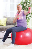 Senior woman sitting on gym ball, and exercise with weights at h — Stock Photo