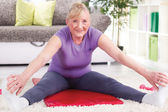 Senior woman stretching and exercise at home — Stock Photo