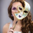 Beautiful young woman with mysterious venetian mask  — Stock Photo