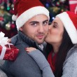 Girl surprising a boy with a gift in Christmas night — Stock Photo