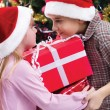 Little boy and girl smiling with present near the Christmas tree — Stock Photo