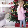 Little girl at home decorating the Christmas tree — Stockfoto