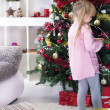 Little girl at home decorating the Christmas tree — ストック写真