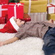 Little smiling boy lying on the floor next to the New Year's gif — Stockfoto
