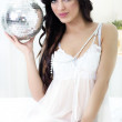 Beautiful young sexy woman holding disco ball — Stock Photo #36359455