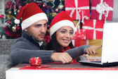 Happy smiling couple using a laptop at home in Christmas — Stock Photo