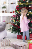 Little girl at home decorating the Christmas tree — Stock Photo