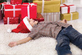 Little smiling boy lying on the floor next to the New Year's gif — Stock Photo