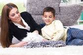 Mom and son caress white Persian cat — Stock Photo