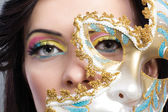 Beautiful young woman with mysterious venetian mask close up — Stock Photo