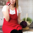 Young modern housewife resting and eating a red apple — Stock Photo