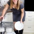 Stock Photo: Sexy housewife takes out plates from dishwasher