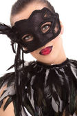 Beautiful young woman in black mysterious venetian mask — Стоковое фото