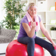 Happy senior woman sitting on gym ball, and exercise with dumbbe — Stock Photo #37580577