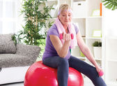 Happy senior woman sitting on gym ball, and exercise with dumbbe — Stock Photo