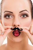 Beautiful girl with perfect skin holding fake mustache — Stock Photo
