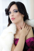 Provocative young woman with white fur around her neck posing — Stock Photo