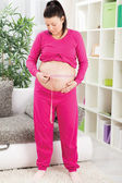 Happy pregnant woman measures her belly — Zdjęcie stockowe