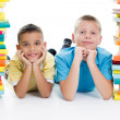 Students sitting behind pile of books on white background — Stok fotoğraf