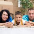 Happy couple with a kid in their new home laying on the floor w — Stockfoto #39931215