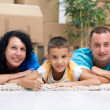Happy couple with a kid in their new home laying on the floor w — Foto Stock #39931215