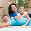 Happy couple with a kid in their new home laying on the floor — Stock Photo