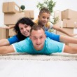Foto Stock: Happy couple with a kid in their new home laying on the floor wi