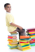 Boy sitting on a pile of books and learn — Stock Photo