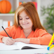 Stock Photo: Cute little red-haired girl doing her homework at home