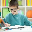 Little boy with glasess at home studying — Stock Photo #40396509